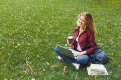 Giovane donna sorridente con il computer portatile all'aperto Fotografia Stock