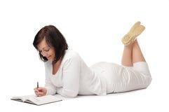 Giovane donna sorridente con il libro e la penna Fotografie Stock Libere da Diritti