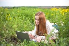 Giovane donna sorridente con il taccuino in parco che esamina computer portatile Immagine Stock