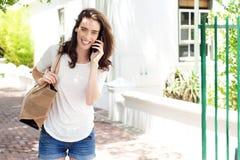 Giovane donna sorridente con il telefono cellulare e la borsa Immagine Stock