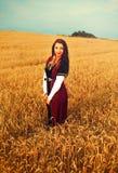 Giovane donna sorridente con il vestito medievale che sta su un giacimento di grano con il tramonto Sfondo naturale Fotografie Stock