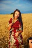 Giovane donna sorridente con il vestito ornamentale che sta su un giacimento di grano con il tramonto E mano del fotografo con la Immagini Stock