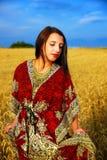 Giovane donna sorridente con il vestito ornamentale che sta su un giacimento di grano con il tramonto Sfondo naturale e cielo blu Fotografia Stock