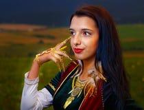 Giovane donna sorridente con il vestito ornamentale e Immagine Stock Libera da Diritti