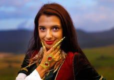 Giovane donna sorridente con il vestito ornamentale e Fotografia Stock