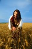 Giovane donna sorridente con il vestito ornamentale e la pelliccia bianca che stanno su un giacimento di grano con il tramonto Sf Fotografia Stock