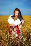 Giovane donna sorridente con il vestito ornamentale e la pelliccia bianca che stanno su un giacimento di grano con il tramonto Sf Immagini Stock