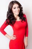 Giovane donna sorridente con il vestito rosso dai capelli marroni ricci lunghi immagini stock