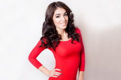 Giovane donna sorridente con il vestito rosso dai capelli marroni ricci lunghi immagini stock libere da diritti