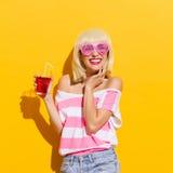 Giovane donna sorridente con la bevanda rossa fresca Fotografie Stock Libere da Diritti