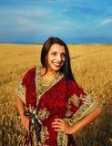 Giovane donna sorridente con la condizione ornamentale del vestito Immagine Stock