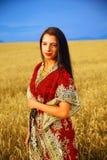 Giovane donna sorridente con la condizione ornamentale del vestito Fotografie Stock