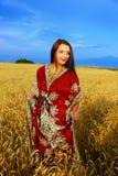 Giovane donna sorridente con la condizione ornamentale del vestito Fotografia Stock Libera da Diritti