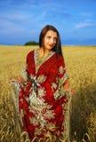 Giovane donna sorridente con la condizione ornamentale del vestito Fotografie Stock Libere da Diritti