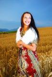 Giovane donna sorridente con la condizione ornamentale del vestito Immagine Stock Libera da Diritti