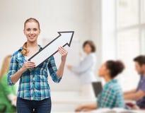 Giovane donna sorridente con la freccia che poiting su Fotografie Stock