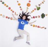 Giovane donna sorridente con la frutta di armi e le verdure stese e fresche nelle linee e nei modelli, colpo dello studio Fotografia Stock