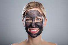 Giovane donna sorridente con la maschera di protezione del carbone attivo immagini stock
