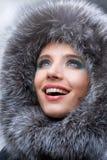 Giovane donna sorridente con un cappuccio della pelliccia Fotografia Stock