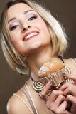 Giovane donna sorridente con un dolce fotografie stock libere da diritti