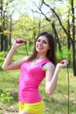 Giovane donna sorridente con un salto della corda in un riassunto Fotografie Stock Libere da Diritti