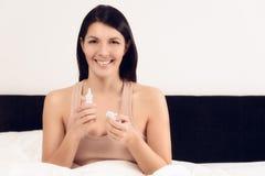 Giovane donna sorridente con una bottiglia di inhalant Immagini Stock Libere da Diritti