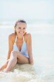 Giovane donna sorridente in costume da bagno che gode della seduta in acqua di mare Fotografie Stock Libere da Diritti
