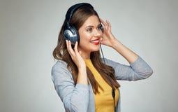 Giovane donna sorridente d'ascolto di musica isolata Fotografia Stock
