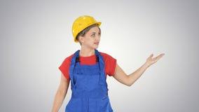 Giovane donna sorridente del lavoratore che parla e che mostra gli oggetti ai suoi lati sul fondo di pendenza fotografie stock libere da diritti