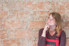 Giovane donna sorridente della testarossa vestita in camici rossi immagini stock
