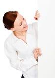 Giovane donna sorridente di affari che esamina un'insegna in bianco Fotografia Stock