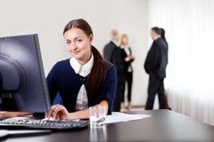 Giovane donna sorridente di affari che per mezzo del calcolatore Immagini Stock Libere da Diritti