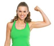 Giovane donna sorridente di forma fisica che mostra il bicipite immagini stock libere da diritti
