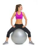 Giovane donna sorridente di forma fisica sulla palla di forma fisica che considera lo spazio della copia Immagine Stock Libera da Diritti