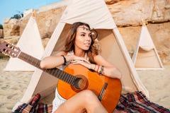 Giovane donna sorridente di hippy che posa con la chitarra alla spiaggia Immagine Stock