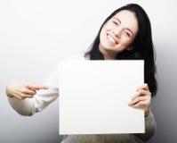 Giovane donna sorridente di stile casuale che mostra insegna in bianco Immagine Stock Libera da Diritti