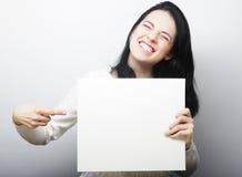 Giovane donna sorridente di stile casuale che mostra insegna in bianco Fotografia Stock Libera da Diritti