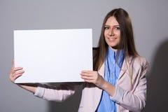 Giovane donna sorridente di stile casuale che mostra insegna in bianco Immagini Stock Libere da Diritti