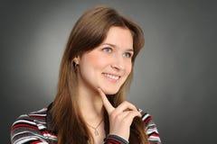 Giovane donna, sorridente ed osservante da parte Fotografia Stock