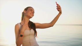 Giovane donna sorridente felice che fa la foto del selfie facendo uso del suo smartphone vicino al mare archivi video