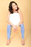 Giovane donna sorridente felice che si siede in un rilassamento bianco della sedia Fotografia Stock Libera da Diritti