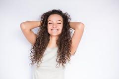 Giovane donna sorridente felice con capelli ricci Fotografia Stock