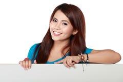Giovane donna sorridente felice di affari che mostra carta in bianco Fotografia Stock