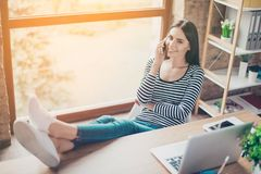 Giovane donna sorridente graziosa nel luogo di lavoro che parla sul telefono mentre Fotografia Stock Libera da Diritti