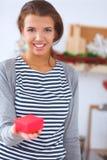 Giovane donna sorridente nella cucina, isolata sopra Fotografia Stock
