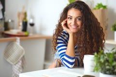 Giovane donna sorridente nella cucina, isolata sopra Immagine Stock