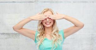 Giovane donna sorridente o ragazza teenager che la copre occhi Fotografia Stock