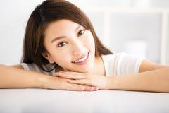 Giovane donna sorridente rilassata in salone Immagine Stock Libera da Diritti