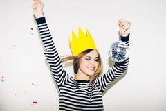 Giovane donna sorridente su fondo bianco che celebra partito, vestito spogliato d'uso e corona di carta gialla, dinamico felice Fotografia Stock Libera da Diritti
