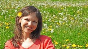 Giovane donna sorridente sul giacimento del dente di leone Fotografie Stock